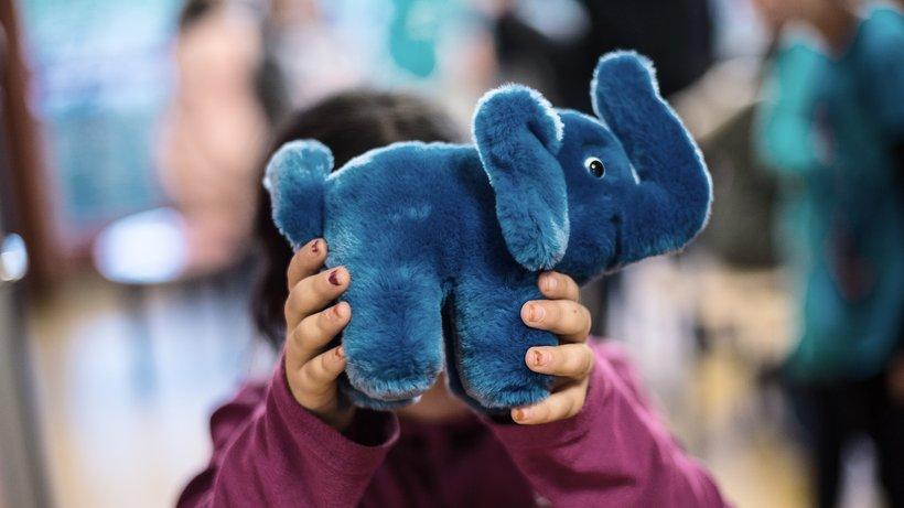 Ein Mädchen hält sich einen blauen Stoffelefanten vor das Gesicht. © Andreas Arnold/dpa