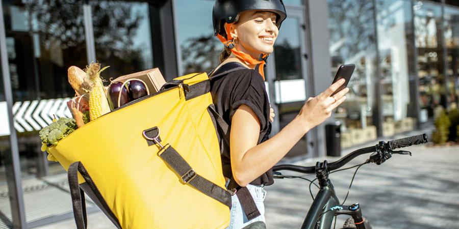 Radfahrerin mit frischem Gemüse im Rucksack © Bild: RossHelen – iStock