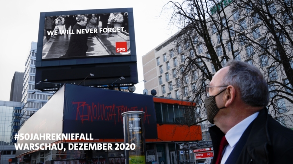 Norbert Walter-Borjans im Dezember 2020 in Warschau. Er schaut sich auf einer öffentlichen Leinwand die Szenen von Willy Brandts Kniefall 1970 an.